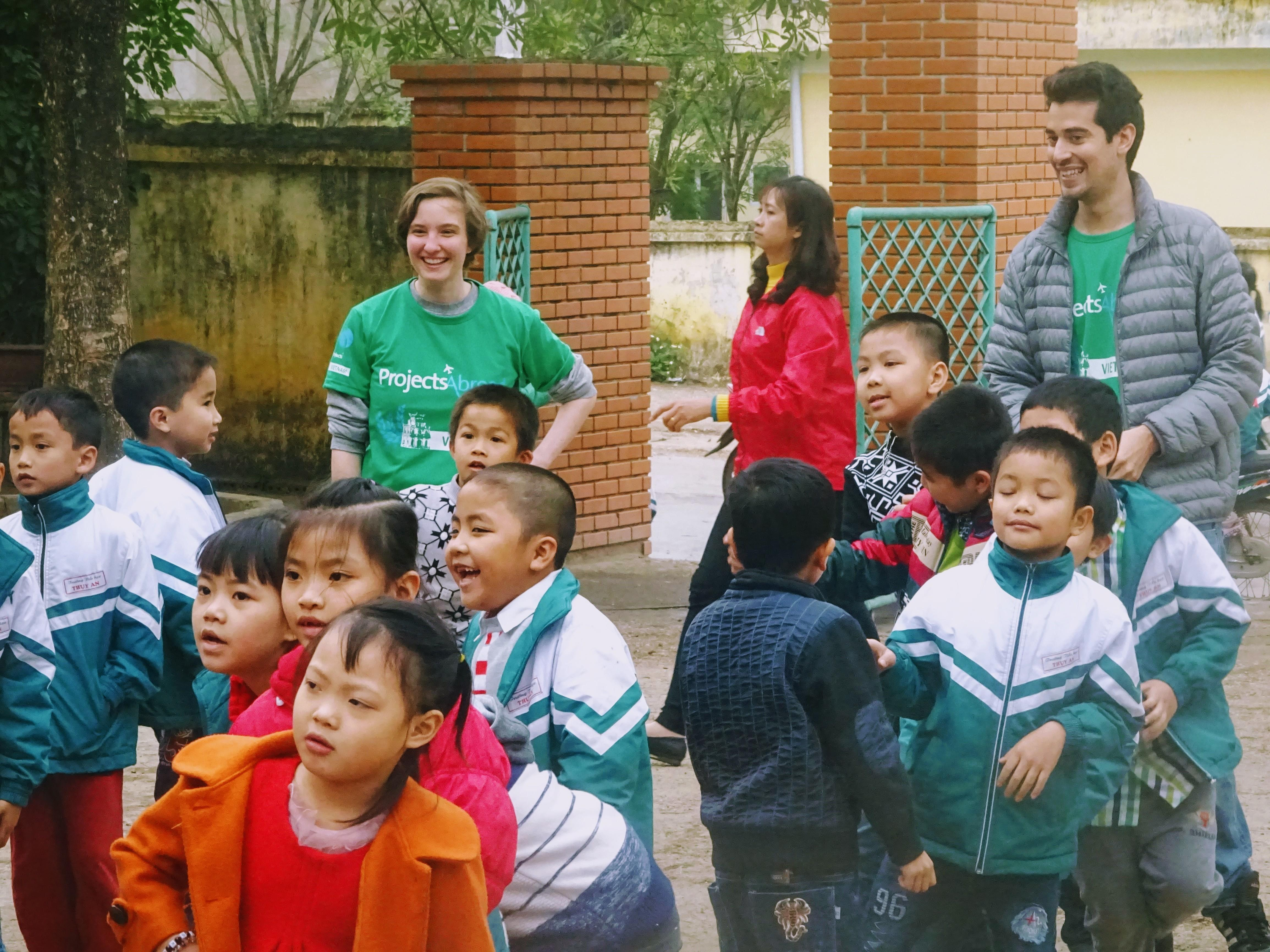 Volunteers play with a group of children outside a care centre at their Childcare placement in Vietnam.